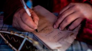 Homem escreve em pedaço de papel