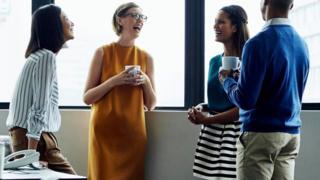 Cuatro trabajadores de pie, tomando café y conversando