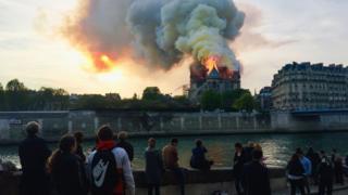 Nas margens do Rio Sena, pessoas observam incêndio da catedral do outro lado, durante entardecer
