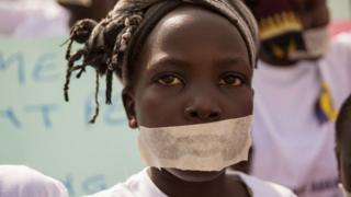 Sandy, 10, wears tape over her mouth as she joins women from more than 40 South Sudanese women's organisations as they march through the city to express the frustration and suffering that women and children face in Juba, South Sudan on December 9, 2017