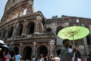 A man holds an umbrella to protect himself from the sun during a ho Summer day in front of the Ancient Colosseum in central Rome
