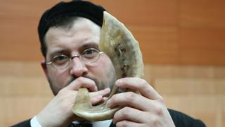 Man blowing a shofar in a synagogue