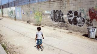 Un niño camina solo en el estado de Tijuana, fronterizo entre México y EE.UU.