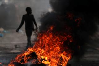 A child walks past a burning barricade during anti-government protests in Port-au-Prince