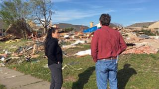 Lindsay Diaz stands with a neighbour outside their demolished home