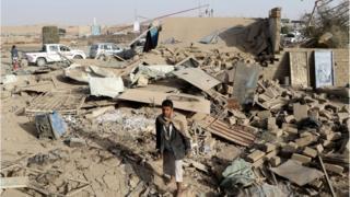 شاب يمشي على حطام منزل بعد غارة لقوات التحالف في محيط صعدة