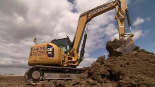 JCB digging a trench and earth bank at a farm