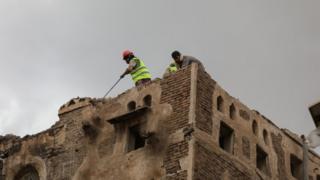 Workers demolish a building damaged by rain in Sanaa