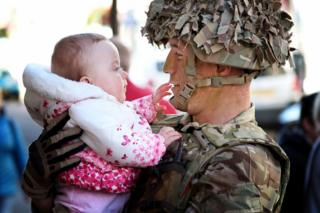 A soldier holds his baby as they look at each other