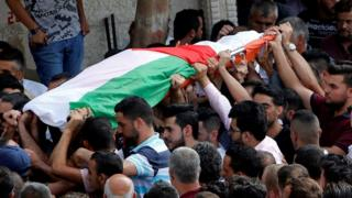Mourners carry the body of Palestinian woman Aisha Rabi, who was killed when a stone hit her car in the occupied West Bank on 12 October