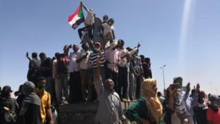 Demonstrators waving flags and shouting outside the army headquarters on March 6
