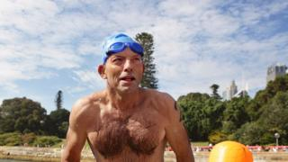 Tony Abbott in a swimming cap and swimmers in a charity swim in 2010