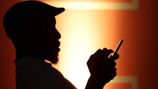 A man in silhouette using a mobile phone in Johannesburg, South Africa - Thursday 30 January 2020