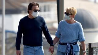 A man and a woman wearing masks in Bournemouth