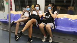 Students wearing protective mask ride the train on June 2, 2020 in Singapore.
