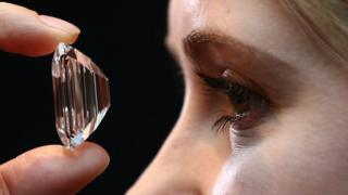Woman staring at a 100 carat diamond