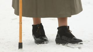 Close-up of elderly woman's shoe in the snow