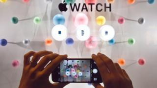 A woman photographs a window display of the Apple watch during the unveiling of the new and highly anticipated product at Saint-Honore street in Paris