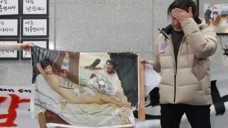 "Artist Lee Koo-Young shows his damaged work ""dirty sleep"", a painting portraying South Korea""s President Park Geun-Hye in the nude, after some conservative protesters damaged the artwork during an exhibition of painting parodies in the lobby of the National Assembly building in Seoul on January 24, 2017."
