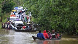 Two boats carrying men float on a lake in Madagascar as several vans and people look on. The chaos was cause by tropical storm Eliakim near Manambonitra, Atsinanana region, Madagascar.