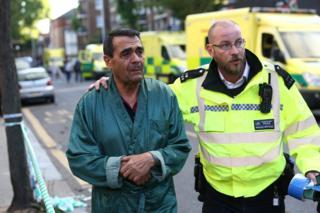 Un inquilino de la Torre Grenfell junto a un policía de Londres.