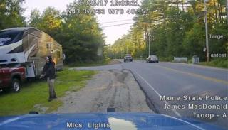 A picture released by Maine State Police shows a man strolling down a street in Hollis, Maine, wearing a clown mask and with a machete taped to his amputated arm