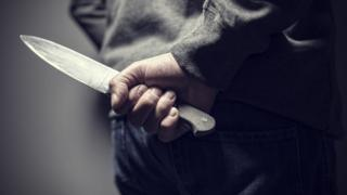 Man with a knife behind his back