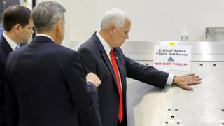 "US Vice-President Mike Pence touches a piece of hardware with a warning label ""Do Not Touch"" at the Kennedy Space Center, 6 July 2017"