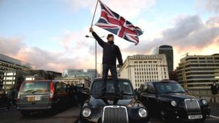 A black cab driver waves a Union Jack flag whilst standing on a taxi.