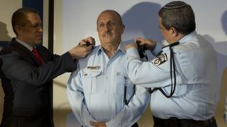 Israeli Public Security Minister Gilad Erdan (left) and Israel Police Chief Roni Alsheikh (right) change the epaulets of newly-named Israeli police Deputy Commissioner Jamal Hakrush (centre), during a ceremony in Tel Aviv (13 April 2016)