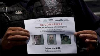 """A Federal Police shows a reward notice for information leading to the capture of drug lord Joaquin """"El Chapo"""" Guzman, in Almoloya, west of Mexico City, on 16 July 2015."""