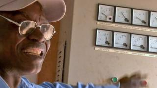 John Mwafute next to a row of dials in his power station