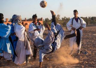 Locals play football during the 15th International Nomad Festival in Mhamid el-Ghizlane in Morocco's southern Sahara desert on March 24, 2018. / AFP PHOTO / FADEL SENNA (Photo credit should read FADEL SENNA/AFP/Getty Images)
