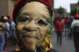 A protester wears a mask depicting South African president Jacob Zuma during a protest march in Pretoria, South Africa, Wednesday, Nov. 2, 2016