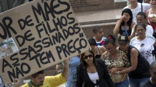 "Man holds sign that reads ""The sadness of mothers of children killed, doesn't have a price"" at funeral for Eduardo Victor. 30 Sept 2015"