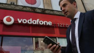 A man uses a smartphone as he walks past a Vodafone store in central London on May 16, 2017.