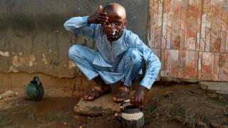 in_pictures A boy performs the ritual ablutions before praying at a mosque to celebrate Eid al-Fitr at a mosque in Kara Ibafo in Ogun State, on May 24, 2020.