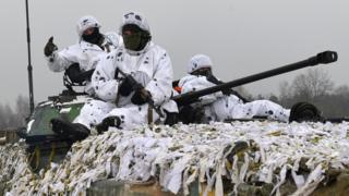 Three heavily armed Ukrainian soldiers dressed in white camouflage space on top of a tank covered with similar white fabric strips, with the cannon of the thought protruding from the divide between men