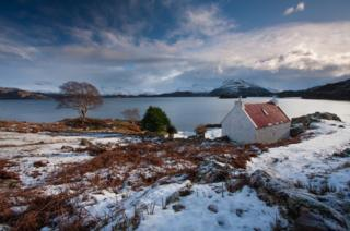 The Red Croft at Ardheslaig on the banks of Loch Shieldaig in Wester Ross, looking over to the Torridon mountains in the distance.