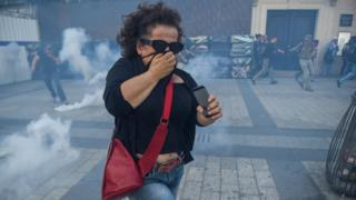 A woman runs from tear gas on the Champs Elysees