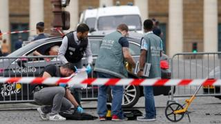 French police look for clues after a car drove through barriers set up for the final stage of the Tour de France in central Paris (26 July 2015)