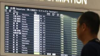 A man looks at the flight information board at the Haneda International airport in Tokyo on 12 October, 2019.