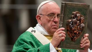 Pope Francis lifting the book of the Gospels during Mass at St Peter's (4 October)