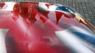 На капоте машины с британским флагом отражается Собор Василия Блаженного
