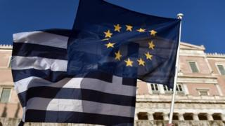 An EU and a Greek flag in front of the Greek parliament in Athens on June 18, 2015