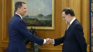 King Felipe VI (L) shakes hands with acting PM Mariano Rajoy (R)
