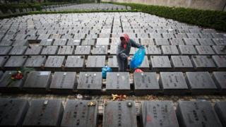 A worker cleans graves during the annual Qingming festival, or Tomb Sweeping Day, at a public cemetery in Shanghai on 6 April 2015.