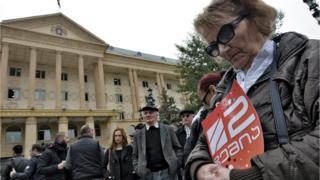 A woman holds a poster with the logo of Rustavi 2 TV station during a protest rally in front of the Tbilisi City Court on October 22, 2015.