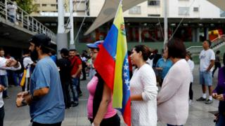 woman with flag waits to vote in Caracas