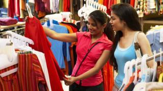 Mulheres vendo roupa em loja